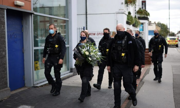 Police officers arrive to pay their respects at the custody center where a British police officer has been shot dead in Croydon, south London, Britain, on Sept. 26, 2020. (Simon Dawson/Reuters)