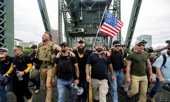 Members of the Proud Boys and Chairman Enrique Tarrio, holding a megaphone, along with other right-wing demonstrators, march across the Hawthorne Bridge during a rally in Portland, Ore., on Aug. 17, 2019. (Noah Berger/AP Photo)