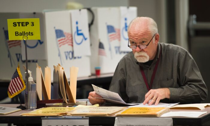 An election worker monitors at an in-person absentee voting station in Fairfax, Va., Oct. 25, 2016. (Andrew Caballero-Reynolds/AFP via Getty Images)