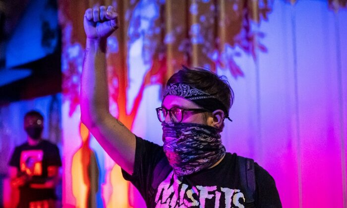 A protester holds his fist in the air in Portland, Ore., on Sept. 6, 2020. (Nathan Howard/Getty Images)