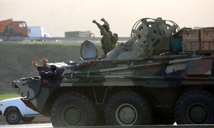 An Azerbaijani service member drives an armored carrier and greets people, who gather on the roadside in Baku, Azerbaijan, on Sept. 27, 2020. (Aziz Karimov/Reuters)