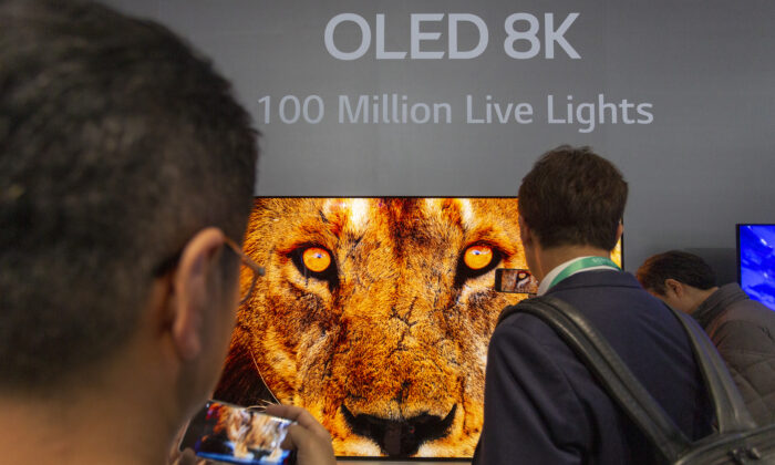 People look at OLED 8K television screens at an exhibit of the 2020 Consumer Electronics Show in Las Vegas, Nev., on Jan. 7, 2020. (David McNew/AFP via Getty Images)