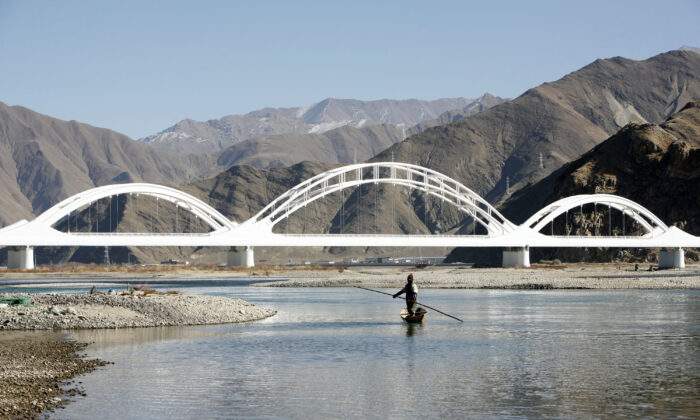 A man from Sichuan Province fishes in the Yarlung Tsangpo River, in Doilungdeqen County of Tibet on Dec. 18, 2008. (China Photos/Getty Images)
