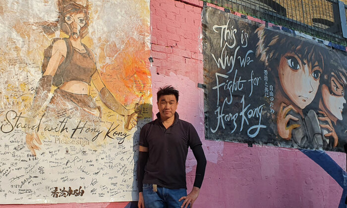Otto Yuen, known in Hong Kong as The Lennon wall painter, poses with his hand-painted posters in London, on Sept. 20, 2020. (Lily Zhou/The Epoch Times)