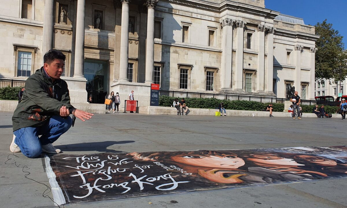Otto Yuen tells stories behind his 10-meter painting about Hong Kong's pro-democracy movement, in Trafalgar Square, London, on Sept. 21, 2020. (Lily Zhou/The Epoch Times)