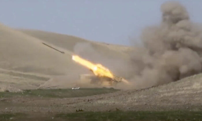 The Azerbaijani military launches a missile at the contact line of the self-proclaimed Republic of Nagorno-Karabakh, as shown in this image taken from footage released by Azerbaijan's Defense Ministry on Sept. 27, 2020. (Azerbaijan's Defense Ministry via AP)