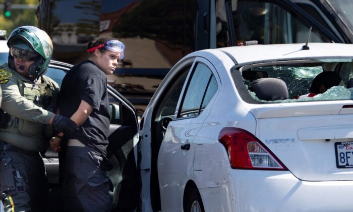 Tatiana Turner is taken into custody after witnesses said she drove her car into a crowd of President Donald Trump supporters in Yorba Linda, Calif., on Sept. 26, 2020. (Mindy Schauer/The Orange County Register via AP)