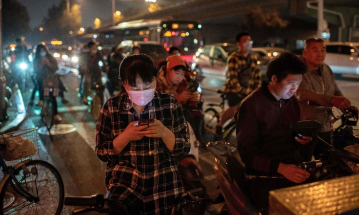A woman wearing a face mask commutes during evening rush hours on a street during a polluted day in Beijing on Sept. 28, 2020. (NICOLAS ASFOURI/AFP via Getty Images)