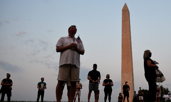 Members of the Covid Memorial Project hold American flags in front of the Washington Monument to commemorate COVID-19 victims, in Washington on Aug. 27, 2020. (Olivier Douliery/AFP via Getty Images)