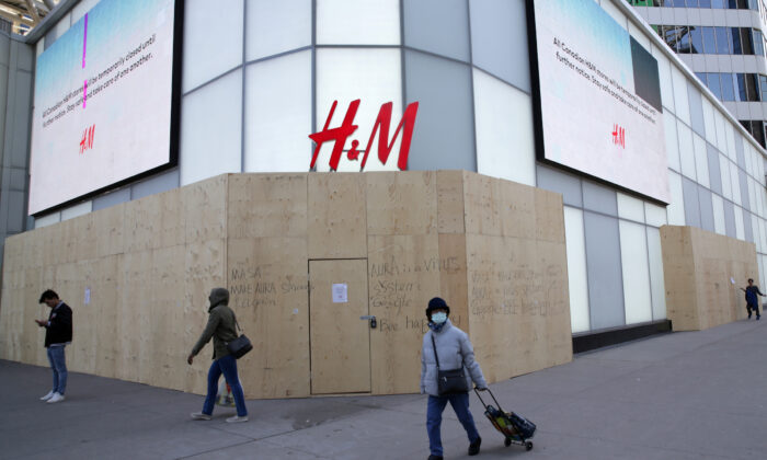 A woman wearing a protective face mask passes the closed and boarded up H&M clothing store at Eaton Centre shopping mall in Toronto on April 6, 2020, during the global outbreak of COVID-19. (REUTERS/Chris Helgren/File Photo)