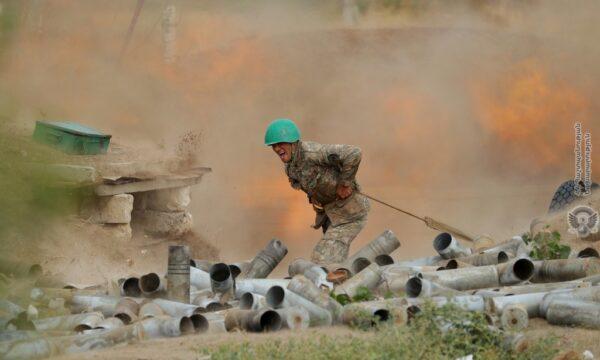 An ethnic Armenian soldier fires an artillery piece