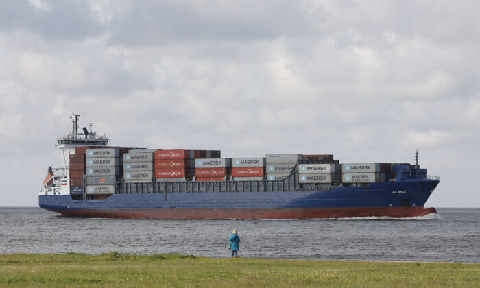 A woman watches a container ship passing by toward the harbor area of the northern German city of Cuxhaven on May 2, 2020. (Morris Mac Matzen/AFP via Getty Images)