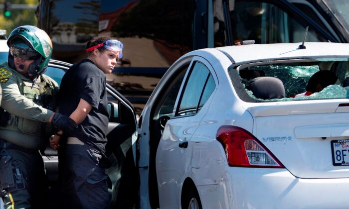 Tatiana Turner is taken into custody after witnesses said she drove her car into a crowd of protesters in Yorba Linda, Calif., on Sept. 26, 2020. (Mindy Schauer/The Orange County Register via AP)