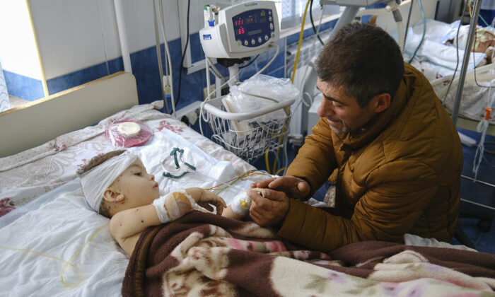 A man speaks with his child, wounded during shelling, in Stepanakert, the self-proclaimed Republic of Nagorno-Karabakh, Azerbaijan on Sept. 28, 2020. (Areg Balayan/PAN Photo via AP)
