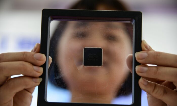 A Chinese employee holds a self-developed chip at a industrial park in Jinan in China's eastern Shandong Province, on May 11, 2019. (STR/AFP via Getty Images)