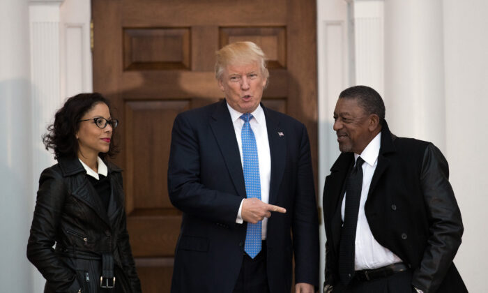 Donald Trump (C) greets Robert Johnson (R), the founder of Black Entertainment Television, and his wife Lauren Wooden (L) at Trump International Golf Club, in Bedminster Township, New Jersey, on Nov. 20, 2016. (Drew Angerer/Getty Images)