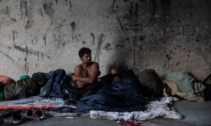 Bangladeshi migrants rest inside an abandoned factory near Velika Kladusa, Bosnia, on Sept. 30, 2020. (Marko Djurica/Reuters)