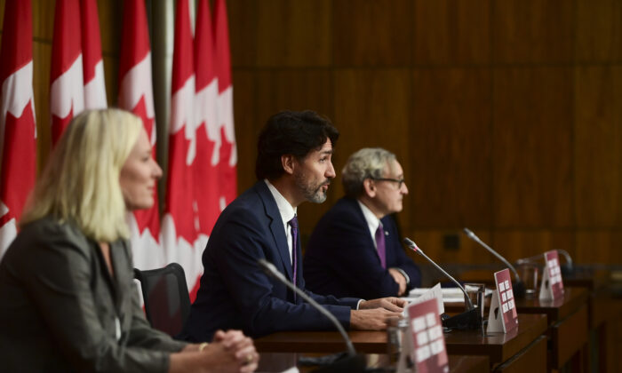 Prime Minister Justin Trudeau is flanked by Minister of Infrastructure and Communities Catherine McKenna (L), and Chair of the Board of the Canada Infrastructure Bank Michael Sabia, during a press conference in Ottawa on Oct. 1, 2020. (Sean Kilpatrick/The Canadian Press)