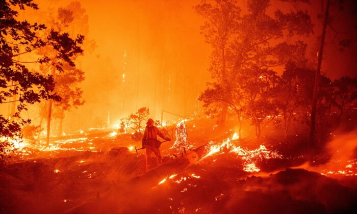 TOPSHOT - A firefighter works the scene as flames push towards homes during the Creek fire in the Cascadel Woods area of unincorporated Madera County, California on Sept. 7, 2020. (Josh Edelson/AFP via Getty Images)