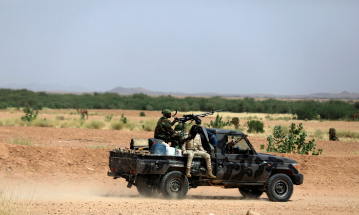 Nigerian army soldiers board a pickup to escort Nigerians heading north towards Libya as they leave Agadez, Niger on Oct. 29, 2019. (Zohra Bensemra/Reuters)