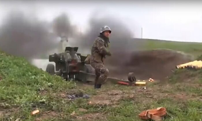 An Armenian serviceman fires a cannon towards Azerbaijan positions at the contact line of the self-proclaimed Republic of Nagorno-Karabakh, Azerbaijan, on Oct. 2, 2020. (Armenian Defense Ministry/AP)