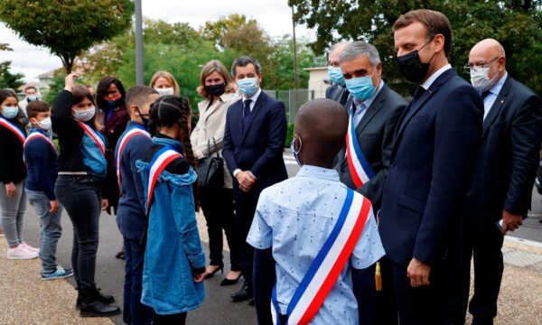 French President Emmanuel Macron speaks to youngsters