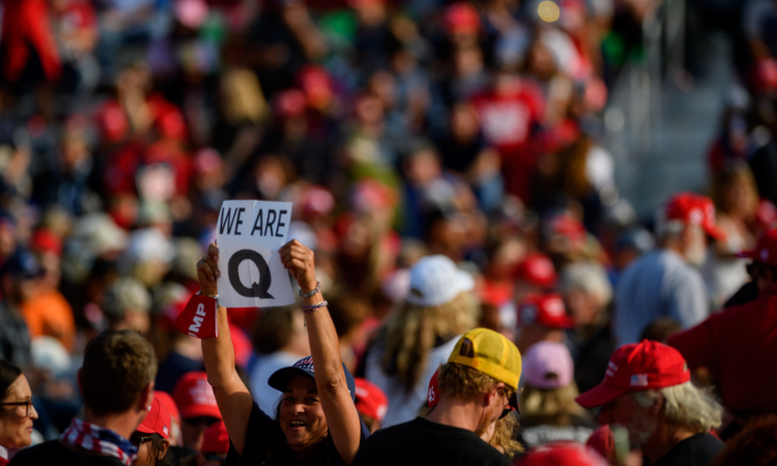 A woman holds up a QAnon sign to the media as attendees wait for President Donald Trump to speak at a campaign rally at Atlantic Aviation in Moon Township, Penn., on Sept. 22, 2020. (Jeff Swensen/Getty Images)