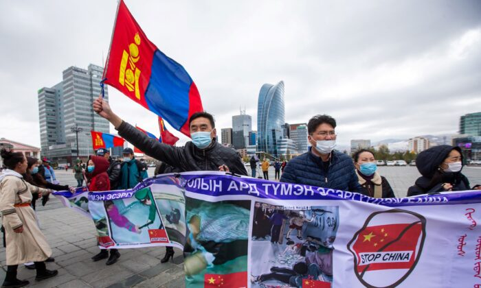 Protestors hold banners and wave the Mongolian flag during a protest in Ulaanbaatar, the capital of Mongolia, against Chinese policies in the neighbouring Chinese province of Inner Mongolia on Oct. 1, 2020. (BYAMBASUREN BYAMBA-OCHIR/AFP via Getty Images)