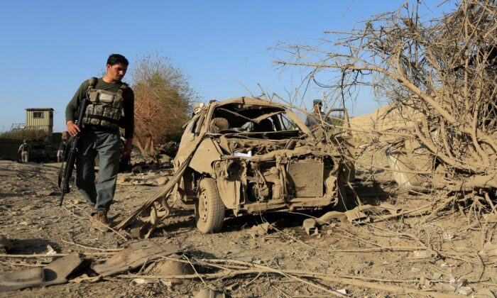 An Afghan police officer inspects the wreckage of a car at the site of a truck bomb blast in Ghani Khel district of Nangarhar province, Afghanistan on Oct. 3, 2020. (Parwiz/Reuters)