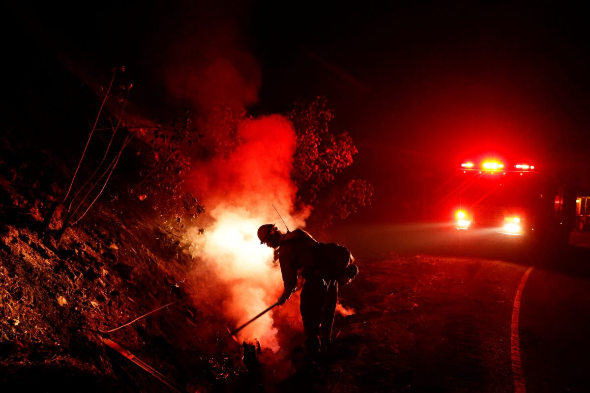 A firefighter mops up a hot spot