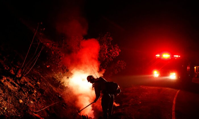 A firefighter mops up a hot spot while battling the Glass Fire in Calistoga, Calif., on Oct. 2, 2020. (Stephen Lam/Reuters)