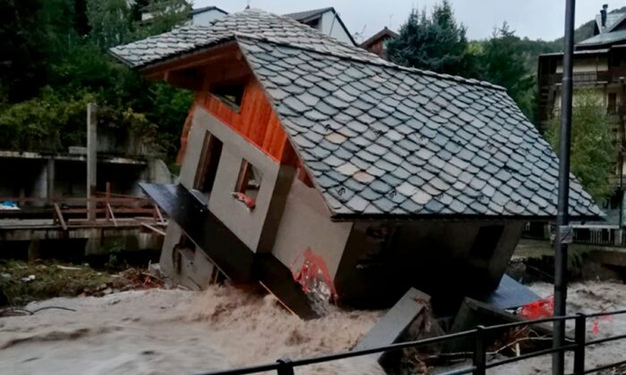 A building is toppled over by the Cervo river in spate due to heavy rains in Biella, northern Italy, on Oct. 3, 2020. (Firefighter Vigili del Fuoco via AP)