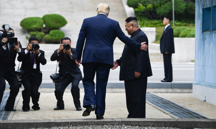 President Donald Trump steps into the northern side of the Military Demarcation Line that divides North and South Korea, as North Korea's leader Kim Jong Un looks on, in the Joint Security Area of Panmunjom in the Demilitarized zone, on June 30, 2019. (Brendan Smialowski/AFP via Getty Images)