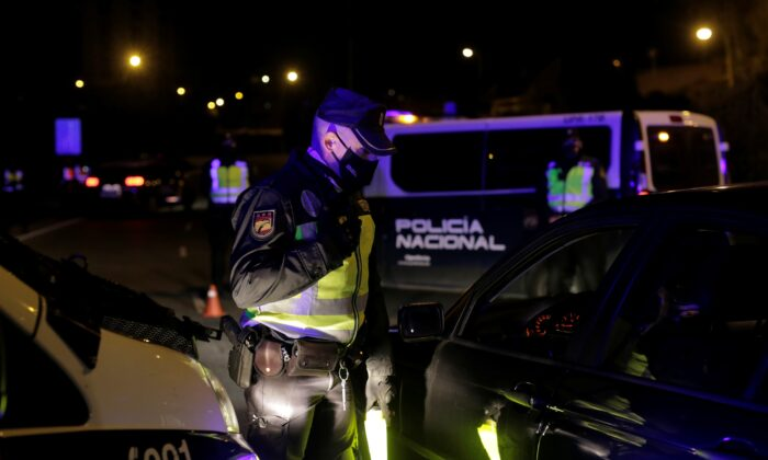 A police officer waits to inspect documents at a checkpoint during a partial lockdown, amid the outbreak of the coronavirus disease (COVID-19), in Madrid, Spain, on Oct. 2, 2020. (Javier Barbancho/Reuters)
