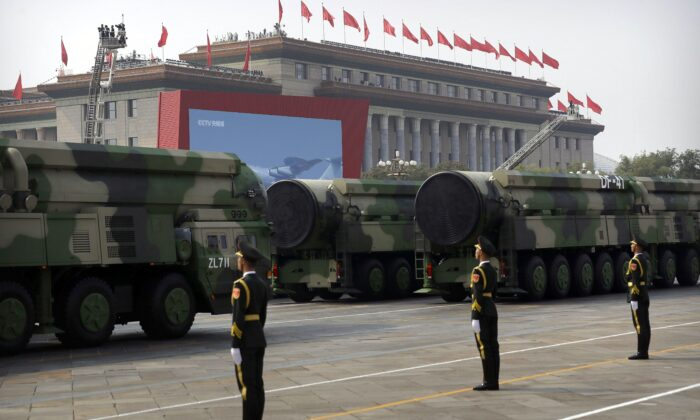Chinese military vehicles carrying DF-41 ballistic missiles roll past the Great Hall of the People during a parade to commemorate the 70th anniversary of the founding of communist China, in Beijing on Oct. 1, 2019. (AP Photo/Mark Schiefelbein)