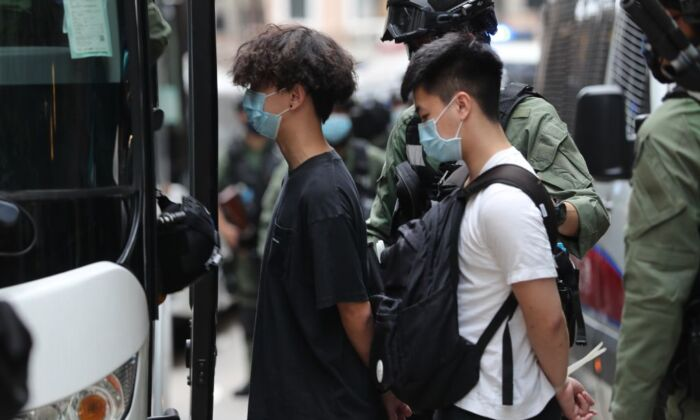 Police officers escort men into a police van following a demonstration in Hong Kong on Oct. 1, 2020. (May James/AFP via Getty Images)
