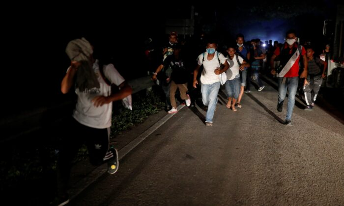 Honduran migrants trying to reach the U.S. run away after hurling stones to Guatemalan soldiers blocking a road to stop migrants from reach the Mexico's border, in San Pedro Cadenas, Izabal, Guatemala, on Oct. 2, 2020. (Luis Echeverria/Reuters)