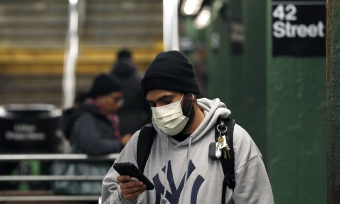 A man wearing a mask uses his phone in the Times Square subway station, as people react to COVID-19 in New York City on March 19, 2020. (Lucas Jackson/Reuters)