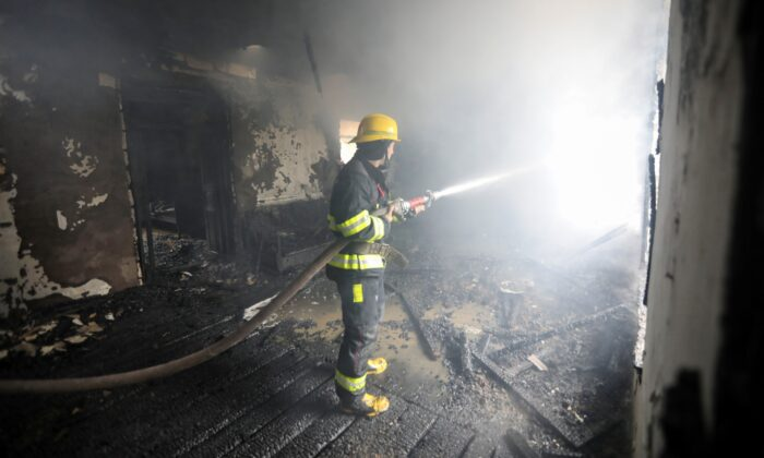 A firefighter extinguishes a fire in a house caused by shelling in the fighting over the breakaway region of Nagorno-Karabakh in the town of Barda, Azerbaijan, on Oct. 5, 2020. (Aziz Karimov/Reuters)