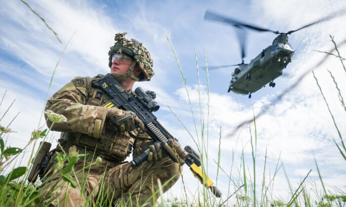 Private Patrick Rodgers of Britain's Anglian Regiment, 2nd Battalion, maintains the perimeter as a Chinook helicopter carries out a medical evacuation during a military exercise on Salisbury Plains near Warminster, England, on July 23, 2020. (Leon Neal/Getty Images)
