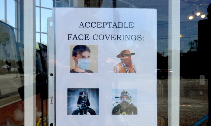 A sign in the window of the O'Gara and Wilson Antiquarian Booksellers bookstore asks customers entering the store to wear face masks in Chesterton, Ind., on May 13, 2020. (Scott Olson/Getty Images)