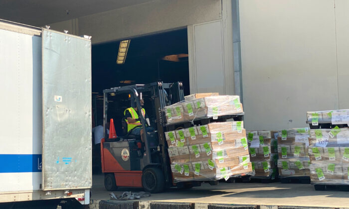 A forklift prepares to load mail-in ballots onto a truck at a loading dock outside the Orange County Registrar's office in Santa Ana, Calif., on Oct. 5, 2020. (Jamie Joseph/The Epoch Times)