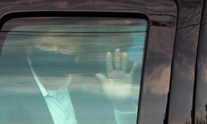 President Donald Trump waves to supporters as he briefly rides by in the presidential motorcade in front of Walter Reed National Military Medical Center, where he is being treated for COVID-19, in Bethesda, Md., on Oct. 4, 2020. (Cheriss May/Reuters)