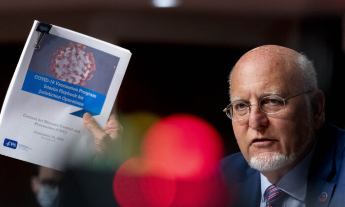 Centers for Disease Control and Prevention (CDC) Director Dr. Robert Redfield holds up a CDC document while he speaks on September 16, 2020 in Washington, DC.  (Photo by Andrew Harnik-Pool/Getty Images)