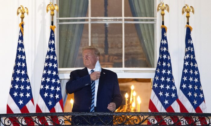 President Donald Trump removes his mask upon return to the White House from Walter Reed National Military Medical Center in Washington on Oct. 5, 2020. (Win McNamee/Getty Images)