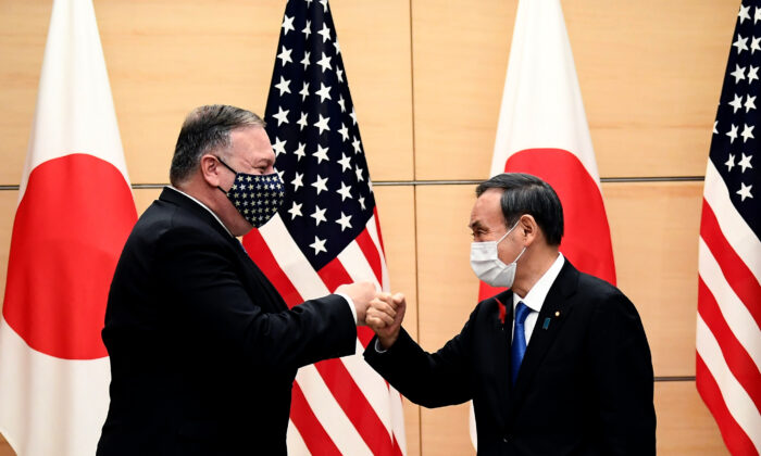 Japan's Prime Minister Yoshihide Suga (R) and U.S. Secretary of State Mike Pompeo (L) bump fists as they meet at the prime minister's office in Tokyo on Oct. 6, 2020. (Charly Triballeau/POOL/AFP via Getty Images)