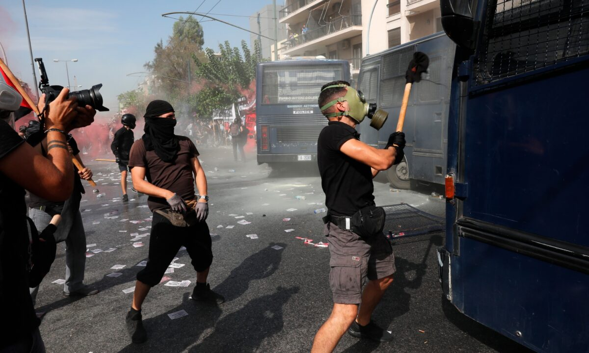A masked protester tries to damage a police vehicle
