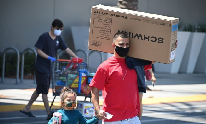 A shopper carries merchandise as he walks to his car in Burbank, Calif., on July 22, 2020. (Robyn Beck/AFP via Getty Images)