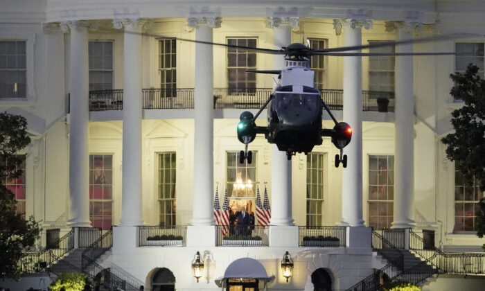 President Donald Trump stands on the Truman Balcony as Marine One takes off from the South Lawn of the White House in Washington, DC on Oct. 5, 2020. (Drew Angerer/Getty Images)