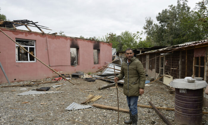 A man stands in front of a house damaged by shelling during the ongoing fighting between Armenia and Azerbaijan over the breakaway Nagorno-Karabakh region, in the village of Alkhanly in Azerbaijan's Fuzuli district on Oct. 7, 2020. (Tofik Babayev/AFP via Getty Images)